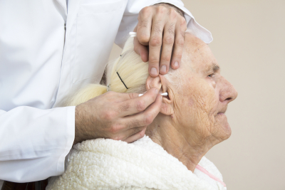 cleaning the ears of an old woman