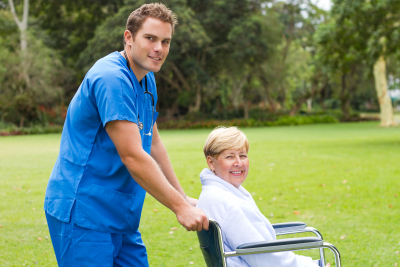 young male nurse pushing senior patient on wheelchair
