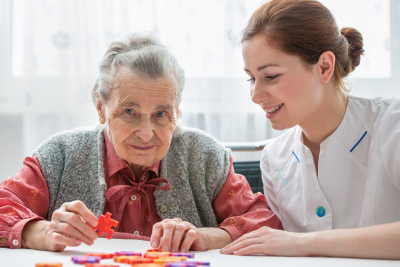 nurse playing jigsaw puzzle with senior woman