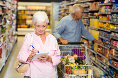 senior woman with shopping list in supermarket